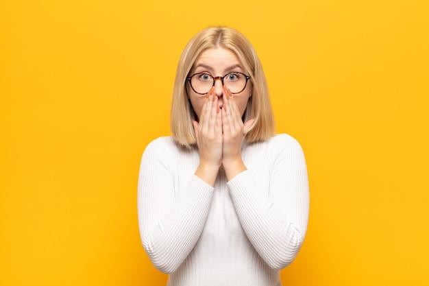 Femme blonde se sentir inquiet, bouleversé et effrayé, couvrant la bouche avec les mains, l'air anxieux et ayant foiré