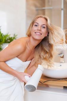 Femme blonde séchant les cheveux après la douche