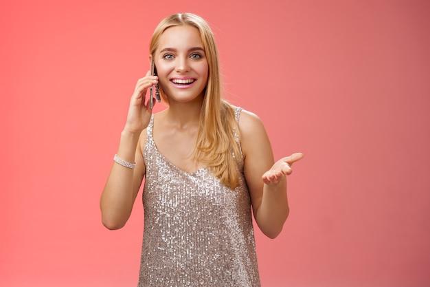 Une femme blonde séduisante et bavarde joyeuse qui parle d'un smartphone ami faisant des gestes amusés souriant largement racontant de nouvelles rumeurs après la fête vêtue d'une robe élégante argentée, fond rouge.