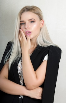 Femme blonde séduisante avec le maquillage naturel portant le costume noir et le chemisier de dentelle