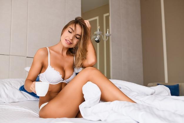 Une femme blonde séduisante en sous-vêtements en dentelle blanche est assise dans son lit avec une couverture blanche et une tasse de café, de thé, une maison de luxe, un hôtel, une chambre d'appartement, une belle matinée avec une dame sexy