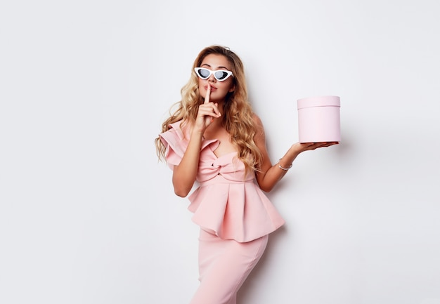 Femme blonde séduisante tenant une boîte-cadeau et posant en robe rose sur un mur blanc. concept de shopping et de célébration. lunettes de soleil à la mode.