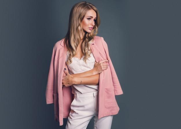 Femme blonde séduisante en veste rose posant