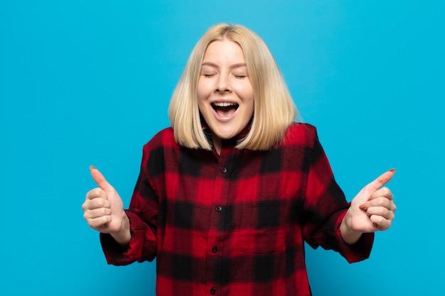Femme blonde semblant extrêmement heureuse et surprise, célébrant le succès, criant et sautant