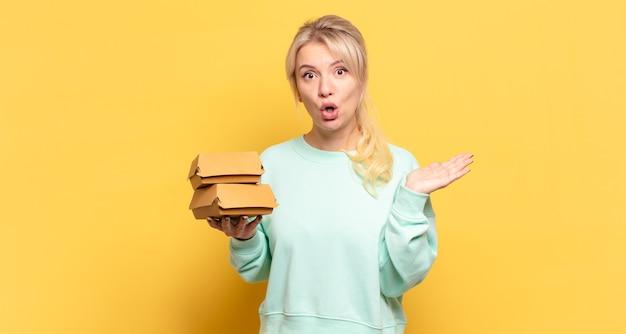 Femme blonde semblant surprise et choquée, avec la mâchoire tombée tenant un objet avec une main ouverte sur le côté