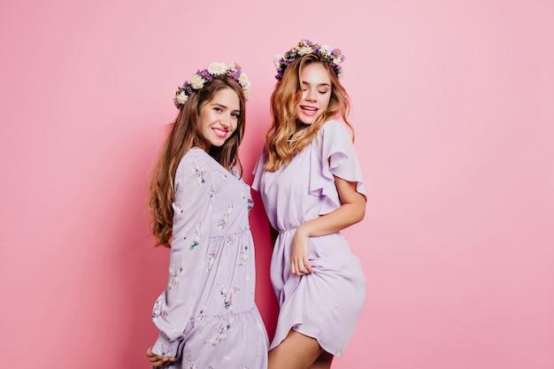 Femme blonde sensuelle en guirlande de fleurs s'amusant avec soeur