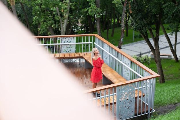 Femme blonde sensuelle vêtue d'une robe rouge à la mode, posant sur le pont en bois avec balustrade