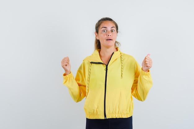 Femme blonde serrant les poings en blouson aviateur jaune et pantalon noir et à heureux