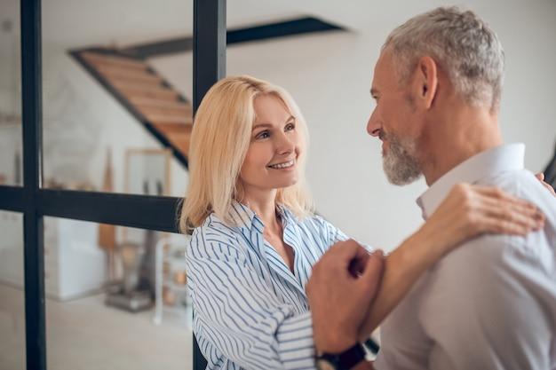 Femme blonde serrant son petit ami et souriant joyeusement
