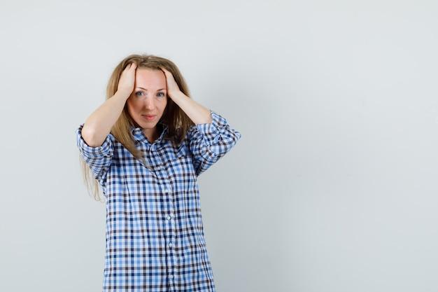 Femme blonde serrant la tête dans les mains en chemise et à l'élégante,