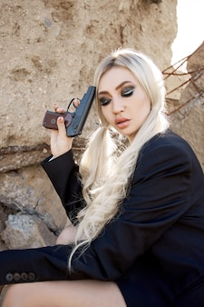 Femme blonde sexy avec une arme à feu dans ses mains