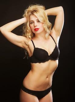 Femme blonde sexy aux cheveux bouclés en lingerie noire, gros plan