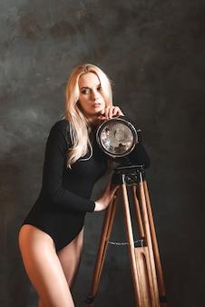 Femme blonde sexy en body à la maison près d'une lampe, lampe de poche. silhouette parfaite, beau corps.