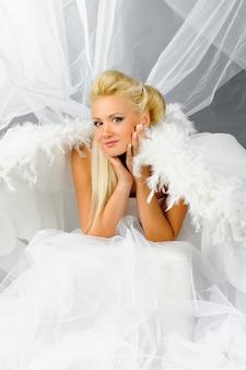 Femme blonde sexy en costume d'ange posant devant la caméra.