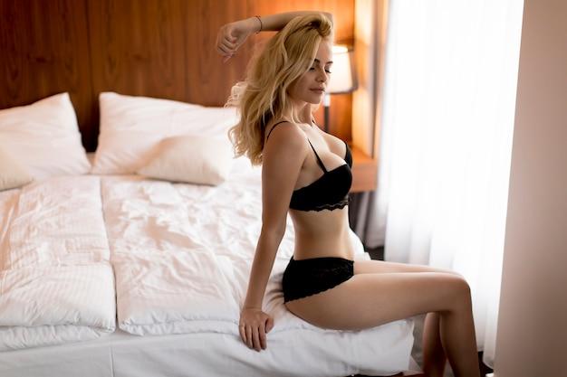 Femme blonde sexy en lingerie assis sur le lit