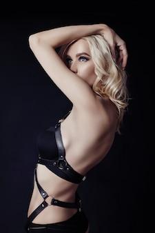 Femme blonde sexy nue en sous-vêtements noirs avec un corps parfait sur fond noir. fille sexy de lingerie érotique. les femmes à la silhouette parfaite