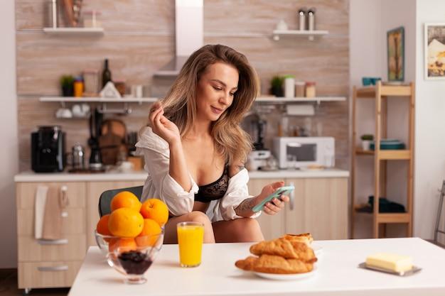Femme blonde sexy recherchant sur le téléphone portant des sous-vêtements sexy