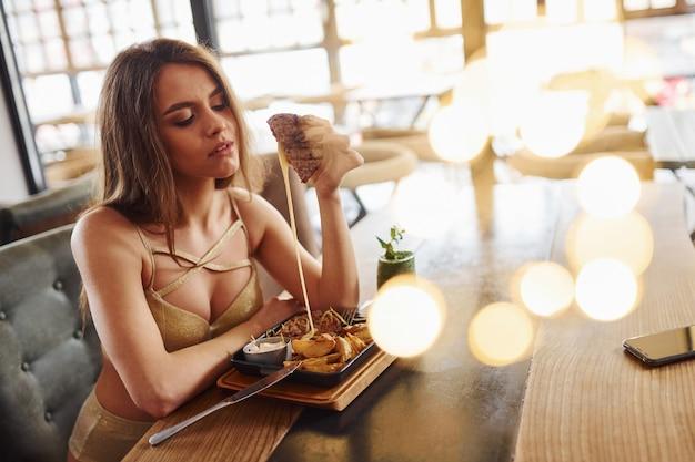 Une femme blonde sexy en vêtements chauds est assise près de la table et mange de la restauration rapide à l'intérieur du café.