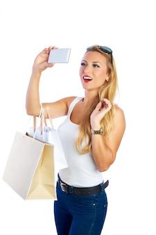 Femme blonde shopaholic sacs et smartphone