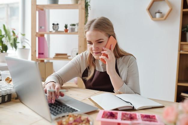 Femme blonde avec smartphone assis par lieu de travail devant un ordinateur portable et appelant ses clients après avoir terminé le travail