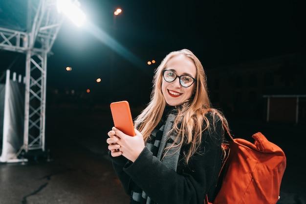 Femme blonde avec un smartphone dans la nuit dans la rue.
