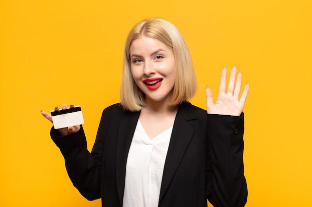 Femme blonde souriant joyeusement et gaiement, agitant la main, vous accueillant et vous saluant, ou vous disant au revoir