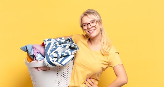 Femme blonde souriant joyeusement avec une main sur la hanche et une attitude confiante, positive, fière et amicale