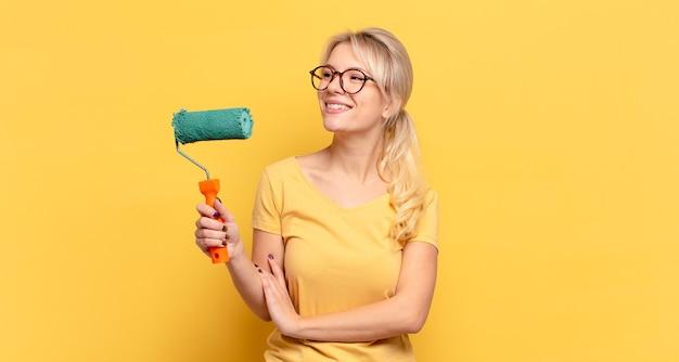 Femme blonde souriant joyeusement et rêvant ou doutant, regardant sur le côté