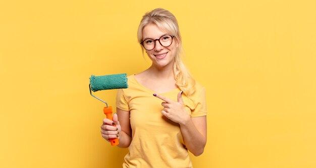 Femme blonde souriant joyeusement, se sentant heureuse et pointant vers le côté et vers le haut, montrant l'objet dans l'espace de copie