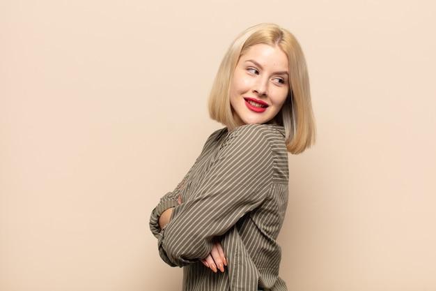 Femme blonde souriant joyeusement, se sentant heureuse, satisfaite et détendue, les bras croisés et regardant sur le côté