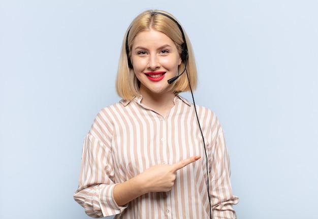 Femme blonde souriant joyeusement, se sentant heureux et pointant vers le côté et vers le haut