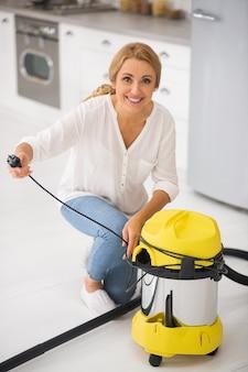 Femme blonde souriante accroupie près de l'aspirateur dans la cuisine tenant le cordon dans les mains