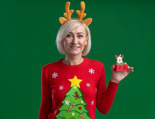 Femme blonde souriante d'âge moyen portant un bandeau en bois de renne de noël et un pull de noël tenant un jouet de renne de noël avec une date semblant isolée sur un mur vert avec un espace de copie