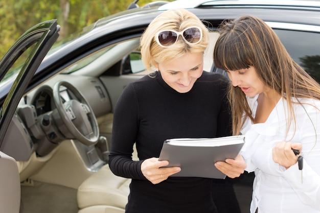 Femme blonde souriante alors qu'elle lit un contrat pour l'achat de sa nouvelle voiture