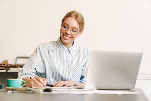 Femme blonde souriante architecte à lunettes travaillant avec un ordinateur portable lors de la conception d'un projet sur le lieu de travail