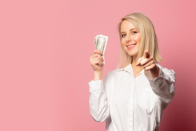 Femme blonde souriante avec de l'argent en dollars
