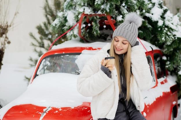 Une femme blonde souriante boit du café au parc d'hiver