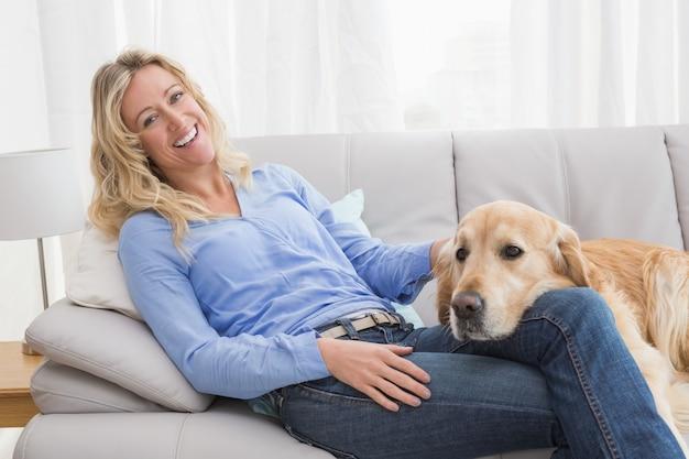 Femme blonde souriante caresser son golden retriever