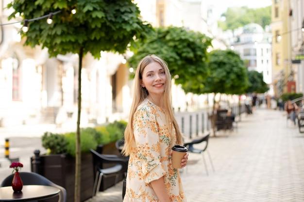 Femme blonde souriante caucasienne vêtue d'une robe buvant du café à emporter et marchant dans la rue sur fond d'arbres verts et de lanternes jaunes, gros plan