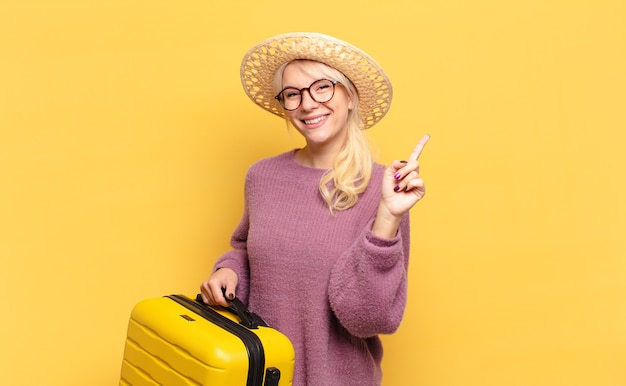 Femme blonde souriante fièrement et avec confiance faisant triomphalement la pose numéro un, se sentant comme un leader