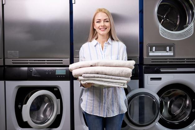 Femme blonde souriante heureuse de faire des corvées à la lessive, tenant une pile de serviettes propres et fraîches. beaucoup de machines à laver en arrière-plan