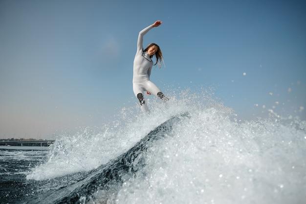 Femme blonde souriante en maillot de bain blanc sautant sur le wakeboard vert sur les genoux pliés