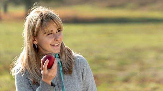 Femme blonde souriante mangeant une pomme délicieuse
