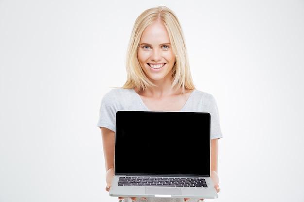 Femme blonde souriante montrant un écran d'ordinateur portable vide isolé sur fond blanc