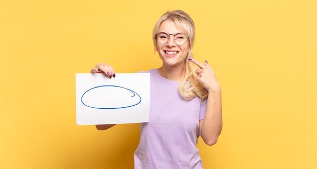Femme blonde souriante pointant avec confiance vers son propre large sourire, attitude positive, détendue et satisfaite