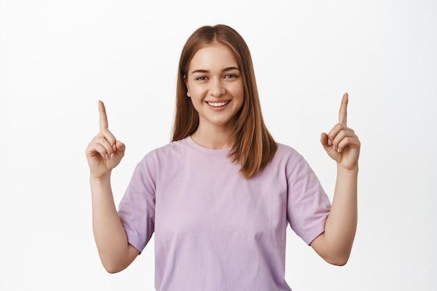 Femme blonde souriante pointant les doigts vers le haut