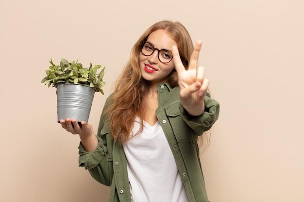 Femme blonde souriante et à la recherche heureuse, insouciante et positive, gesticulant la victoire ou la paix d'une seule main