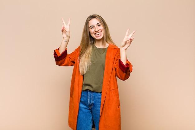 Femme blonde souriante et à la recherche heureuse, sympathique et satisfaite, gesticulant la victoire ou la paix à deux mains