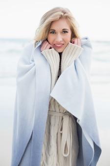 Femme blonde souriante se couvrant dans une couverture