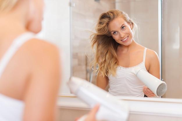 Femme blonde souriante séchant les cheveux le matin